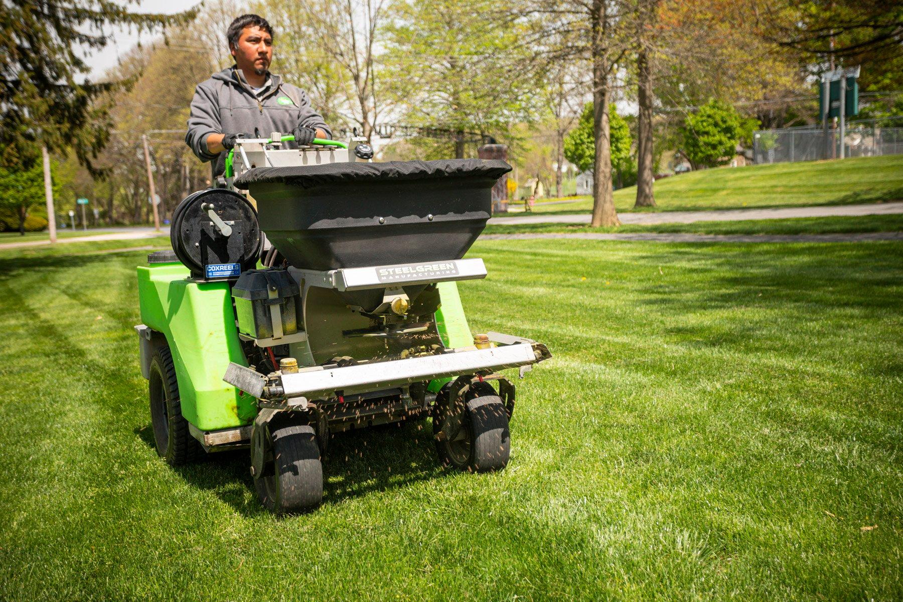 Commercial lawn care technician spreading limestone