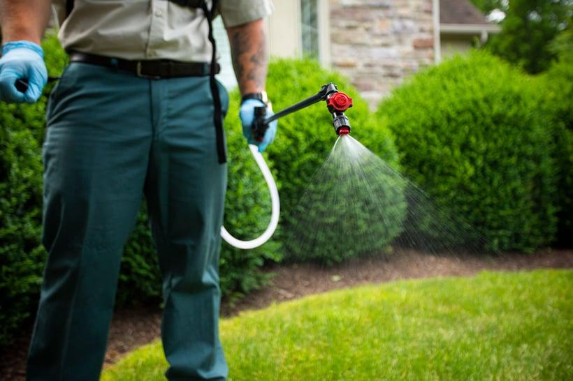 lawn care technician spraying crabgrass preventer