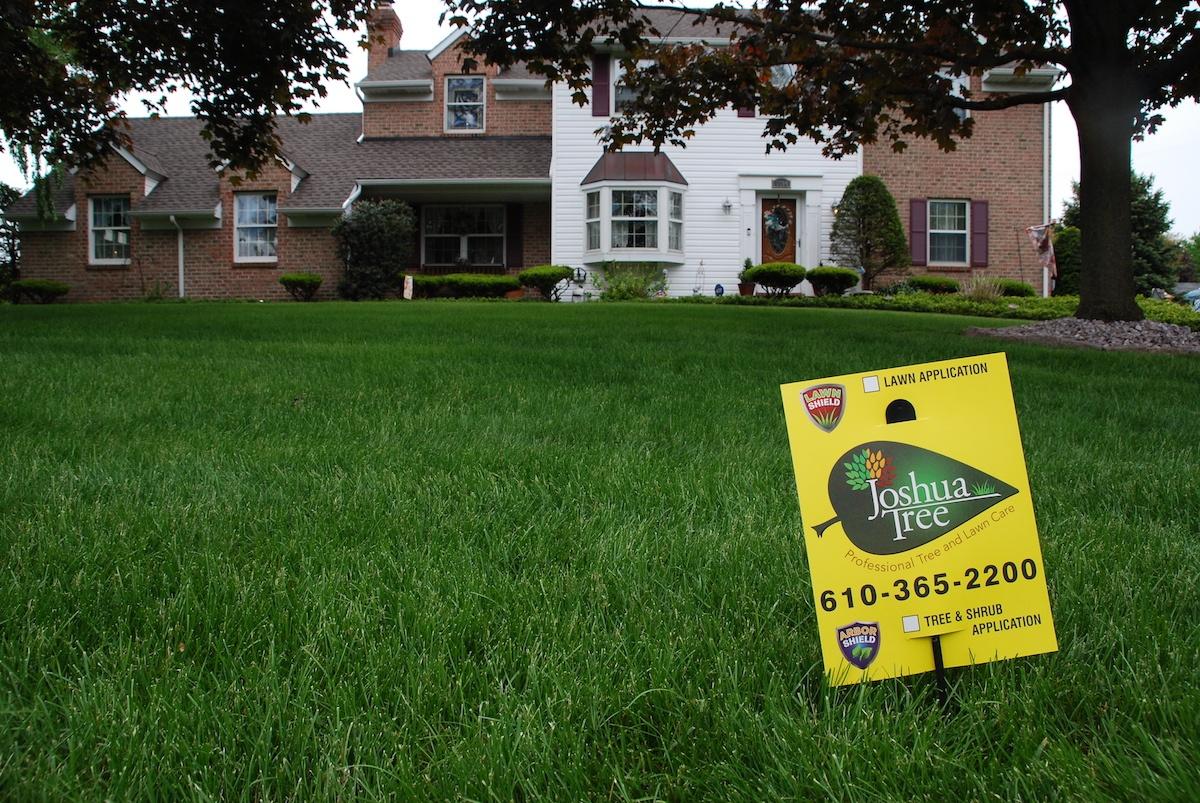 Joshua Tree lawn care sign on nice lawn