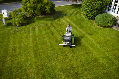 Commercial property lawn care technician treating lawn