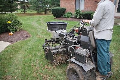 lawn care technician performing lawn aeration services