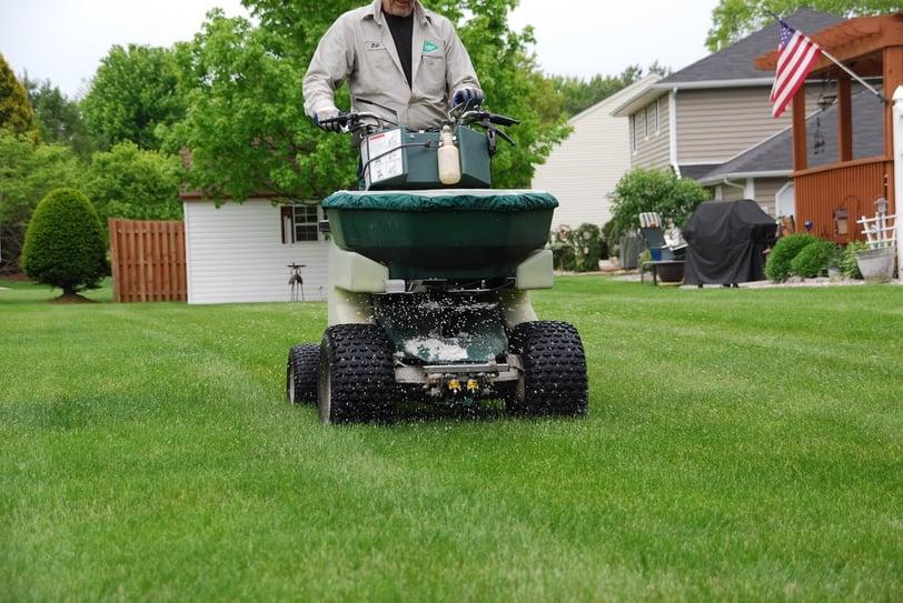 lawn technician applying fertilizer