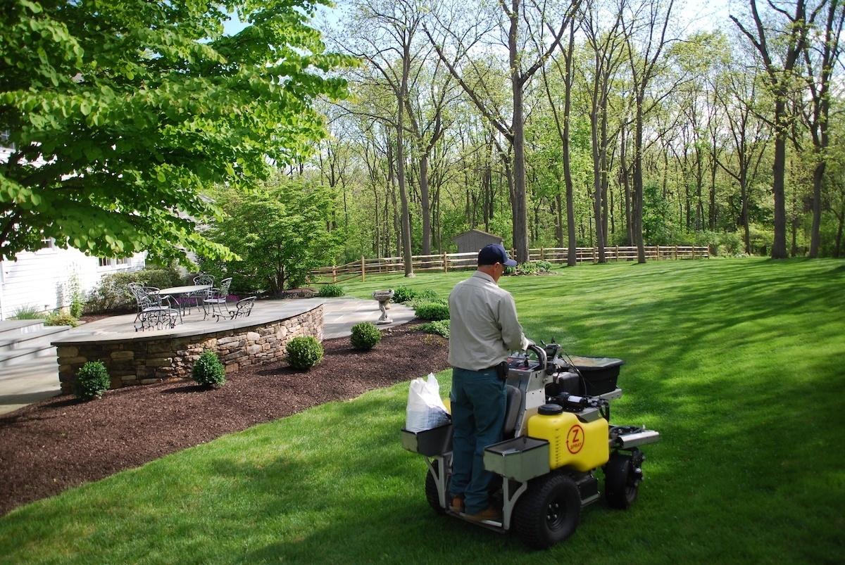 Lawn care technician fertilizing a customers lawn