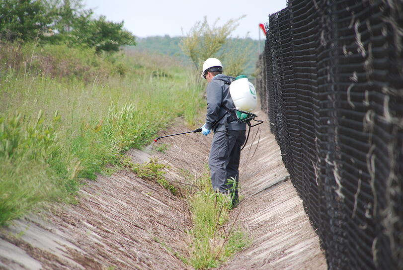 vegetation management technician spraying weed control along fence line
