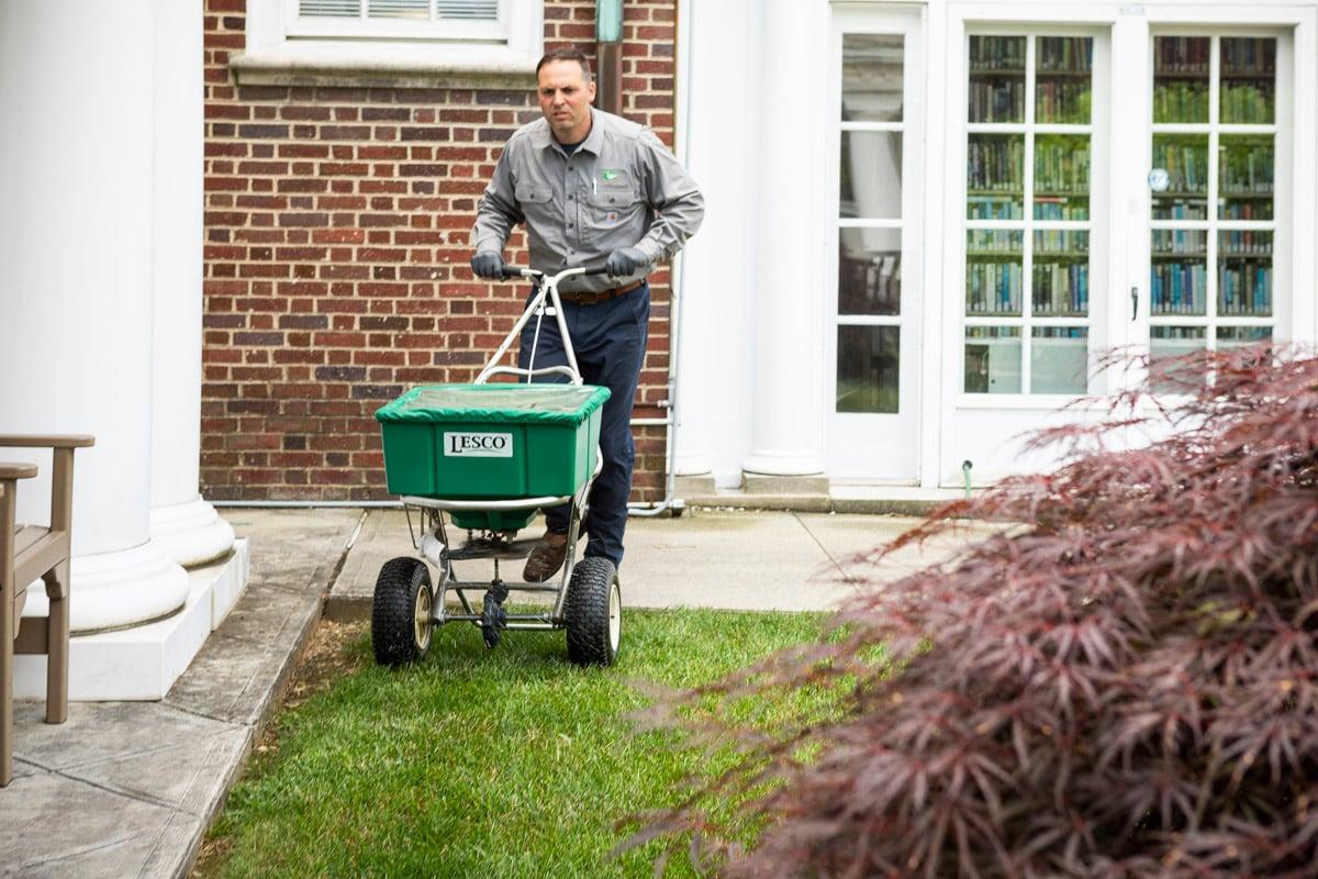 Lawn care technician applying fertilizer with push spreader