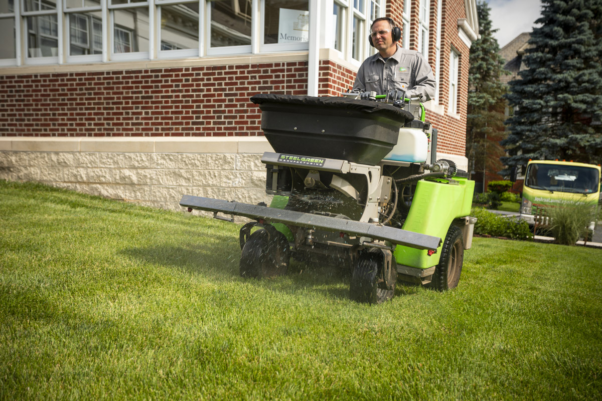 Commercial lawn care technician applying granular fertilizer