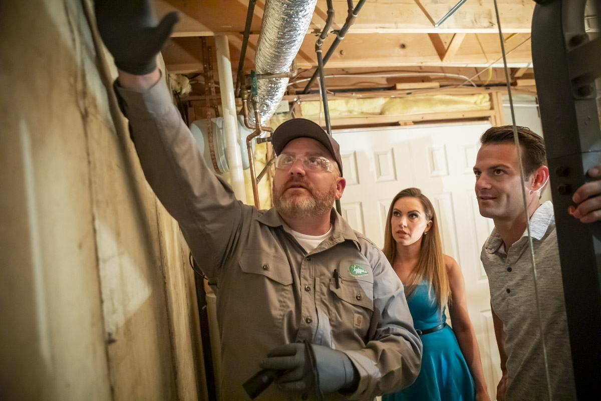 Pest control technician performing home inspection with customers